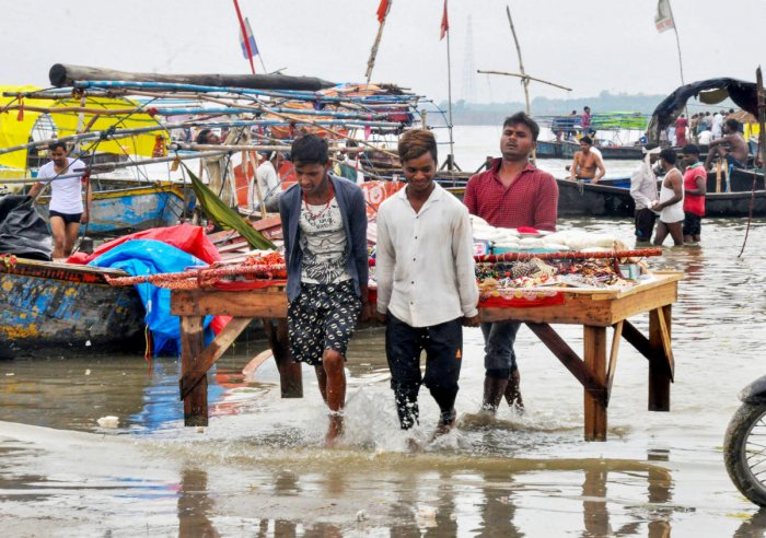 Shopkeepers shift their stalls after an increase in water level at Sangam following monsoon rainfall, in Prayagraj, Thursday, July 11, 2019. (PTI Photo)