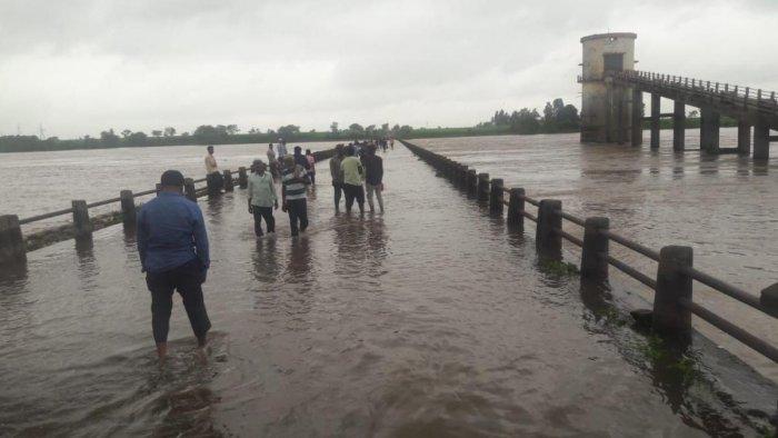 People wade through Kudagi bridge across River Krishna in Raibag taluk of Belagavi district.