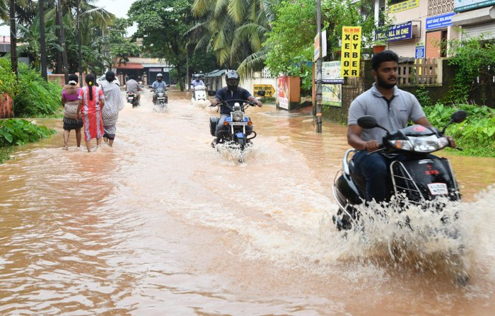 Motorcyclists navigate a flooded road at Malemar on Friday.