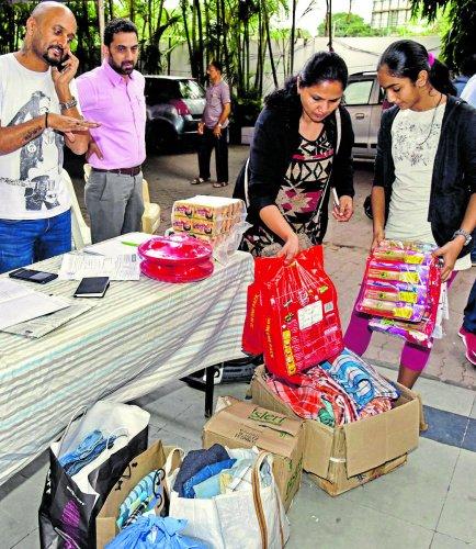 A Kodava Samaja member donates relief materials at the Samaja premises at Vasanthnagar in Bengaluru on Friday. DH PHOTO