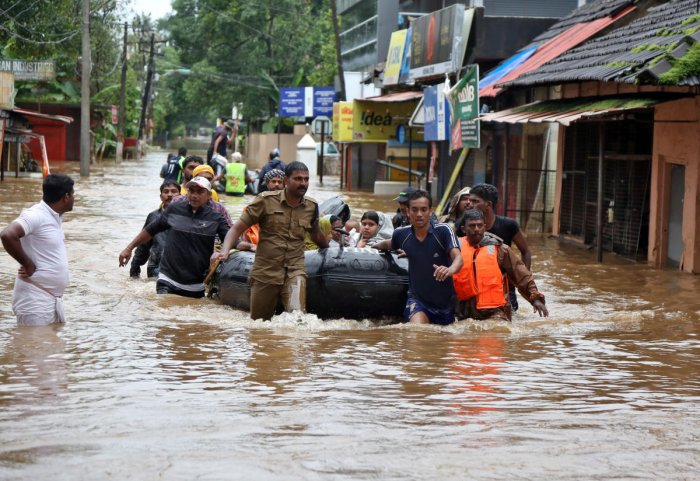 Rescuers evacuate people from a flooded area to a safer place in Aluva in Kerala. (Reuters Photo)