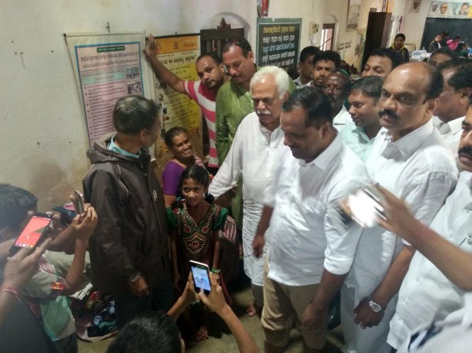 Revenue Minister R V Deshpande, Minister for Urban Development and Housing U T Khader interact with the victims at one of the relief centres in Sampaje on Sunday.