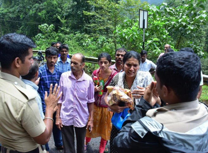 A woman requests police to allow her to travel from Koinadu to Jodupala in Kodagu district on Monday.