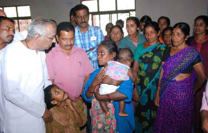 Akhila Bharatha Sharana Sahitya Parishat advisor Go Ru Channabasappa met flood victims at a relief camp in Madikeri on Saturday.