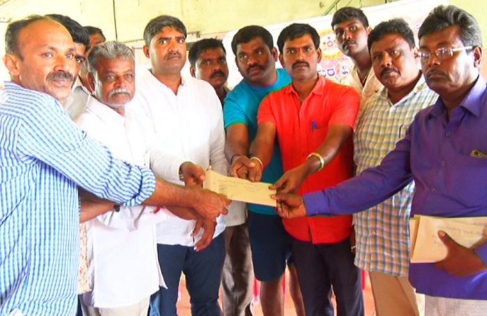 A team from Marenahalli Gram Panchayat distributes aid to flood victims in Madikeri on Sunday.