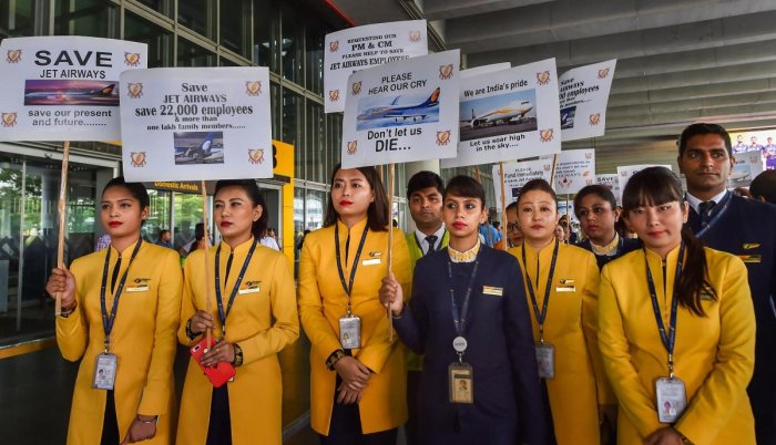 Jet Airways employees display placards during a demonstration to make an appeal for saving the cash-starved airline following the temporary shutdown of its operations, at NSCBI Airport in Kolkata. PTI file photo