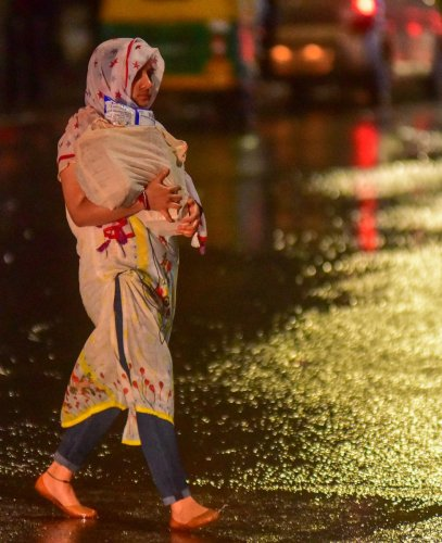 A woman walks through the Residency Road as it rained on Sunday evening. DH photo/Anup R Thippeswamy