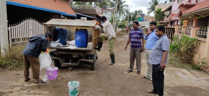 Town Panchayat staff get ready to sprinkle bleaching powder in the residential layouts in Kushalnagar town.
