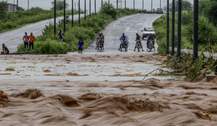 Onlookers and commuters stand next to a flooded water channel flowing over a bridge after heavy rains at New Chandigarh. (AFP photo)