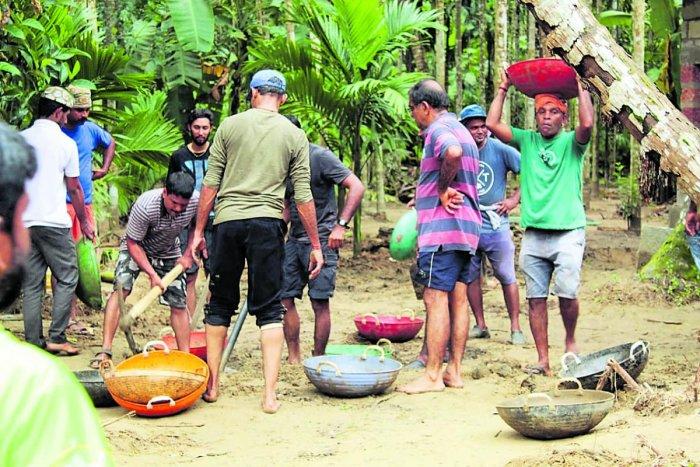 Members of Sahyadri Sanchaya took part in a Shramadan to remove the silt deposited at Raju Gowda's areca plantation near Karyandoor Thodu in Didupe on Sunday.
