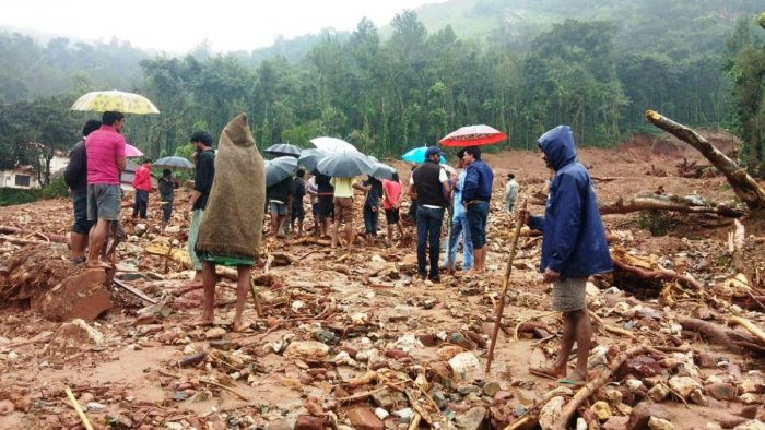 Villagers search the rubble of the damaged houses at Malemane in Chikkamagaluru district.