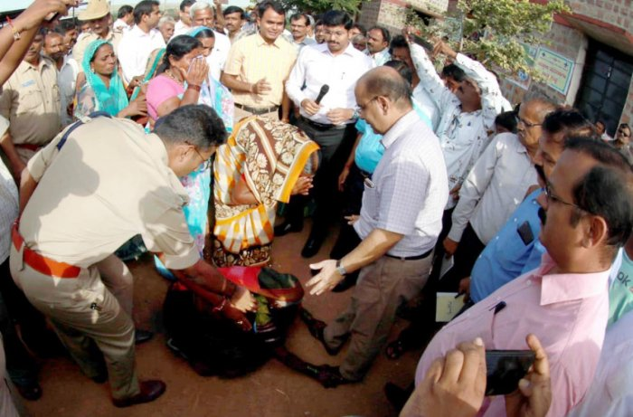 An elderly woman falls at the feet of Sri Prakash, the head of the Central team for assessing flood damage in Aski village of Rabakavi-Banahatti taluk of Bagalkot district on Monday. DH Photo