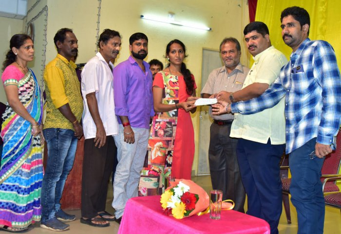 Mangaluru South MLA D Vedavyas Kamath hands over a cheque of compensation to a flood victim in Mangaluru on Monday.