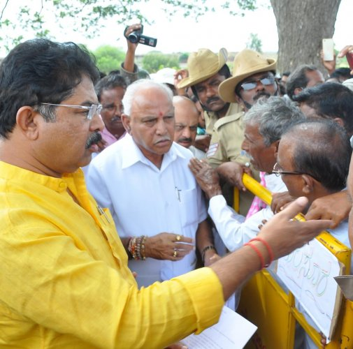 Chief Minister B S Yediyurappa, minister R Ashoka hear grievances of flood-hit villagers in Haveri on Saturday. DH PHOTO