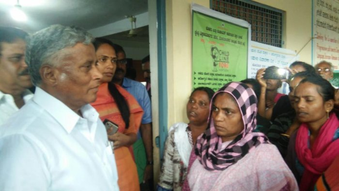 District In-charge Minister V Somanna interacts with the flood victims at the relief centre in Nelyahudikeri on Friday. Deputy Commissioner Annies Kanmani Joy looks on.
