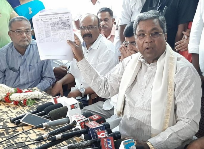 Opposition Leader Siddaramaiah displays a copy of a report on flood-hit victims, during a press conference, in Mandya, on Thursday. Ex-minister M S Athmananda is seen.