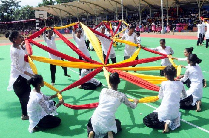 Schoolchildren present a cultural programme as a part of Karnataka Rajyotsava celebrations at Ajjarakadu Grounds in Udupi on Friday.