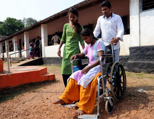 Kamala, an injured citizen, arrives in a wheelchair with the help of her relatives to the voting booth at Kodikal to cast her vote for the MCC Council elections on Tuesday.