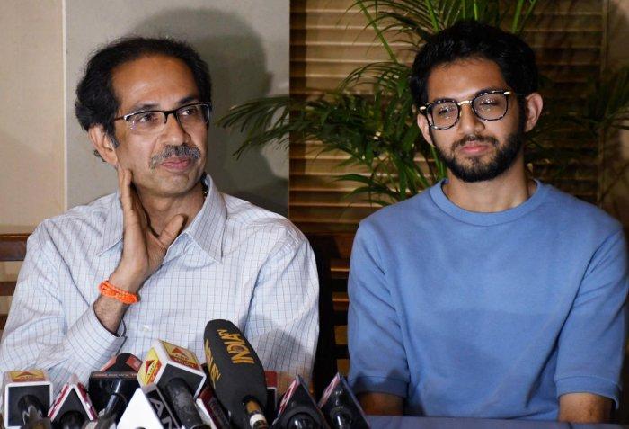 Shiv Sena chief Uddhav Thackeray addresses a press conference as his son and Yuva Sena chief Aaditya Thackeray looks on, in Mumbai. (PTI Photo)