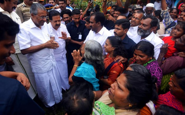 Kerala chief minister Pinarayi Vijayan (L) along with opposition leader Ramesh Chennithala (2L) visit relief camp in Chengamanadu Government Higher Secondary School (HSS) in Ernakulam district. AFP photo.
