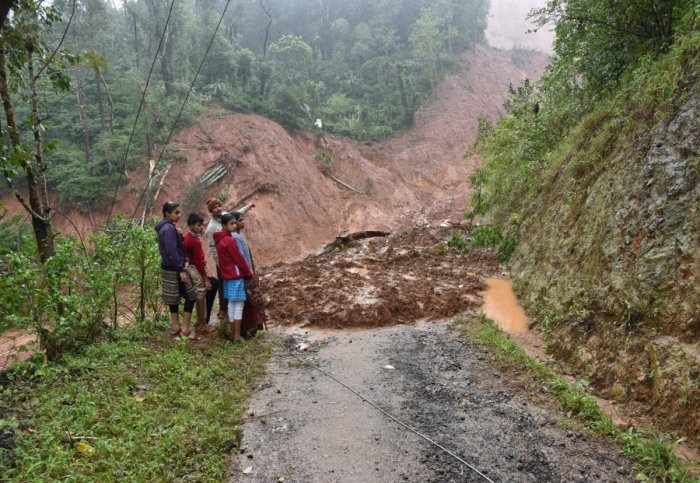 The Poovaiah family shows the part of the hill that collapsed and destroyed their house in Chappe, Hebbettageri, Madikeri on Thursday. Photo/ B H Shivakumar