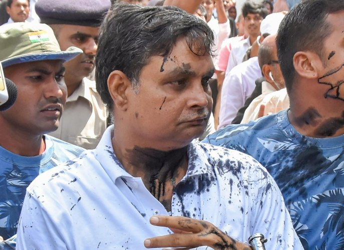 Main accused in the Muzaffarpur shelter home case Brajesh Thakur, after a woman allegedly threw ink on his face while he was being taken to a special POCSO court. (PTI Photo)