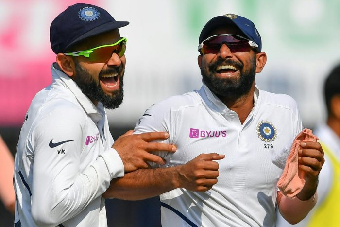India's cricketer Mohammed Shami (R) reacts with captain Virat Kohli (Photo by AFP)