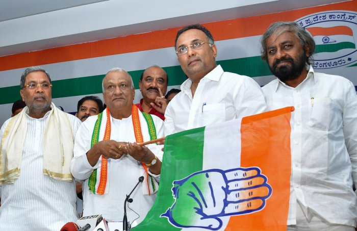 BJP rebel leader Raju Kage holds the Congress flag after it was handed over to him by KPCC chief Dinesh Gundu Rao (second from right) at a ceremony to induct him into the party in Bengaluru on Thursday. Leader of the Opposition Siddaramaiah and KPCC worki