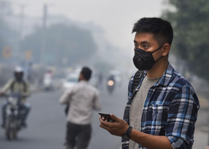 A tourist wears an anti-pollution mask amid heavy smog as the air quality further dips to 'severe' category, in New Delhi. (PTI Photo)