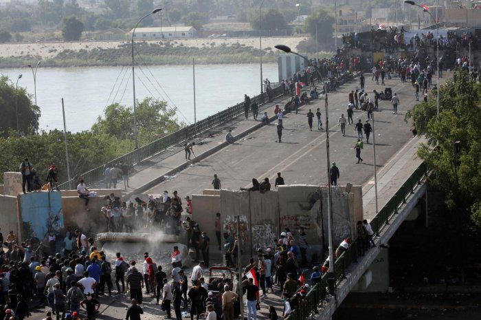 Iraqi demonstrators smash concrete walls at Sinak Bridge during the ongoing anti-government protests, in Baghdad, Iraq November 16, 2019. (REUTERS)