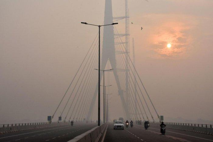 The sun is vaguely seen behind the Signature Bridge amid heavy smog, in New Delhi, Friday, Nov. 15, 2019.. (PTI Photo)