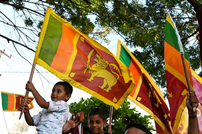 Gotabaya Rajapaksa supporters wave national flags near the election commission office in Colombo on November 17, 2019. (Photo by Reuters)