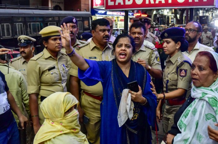 Mumtaz, an IMA investor, protests outside the company's offices in Shivajinagar on Sunday. (Inset) She suffered a gash in her scalp after a stone hit her. DH/Irshad Mahammad