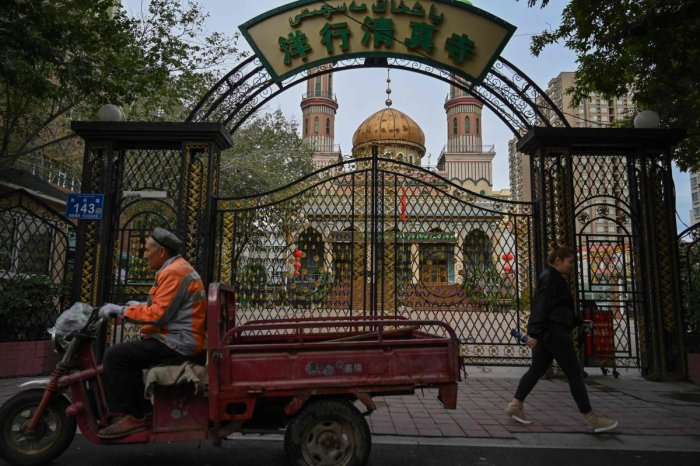 people walking past a mosque in Urumqi, the regional capital of Xinjiang. (Photo by AFP)
