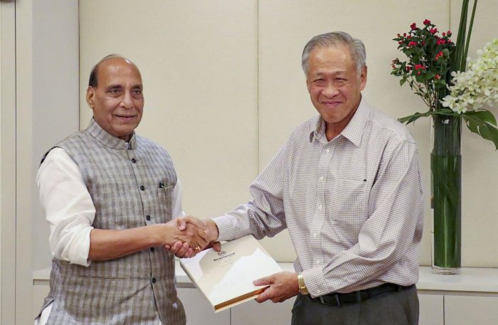 Defence Minister Rajnath Singh sakes hands with Defence Minister of Singapore NG Eng Hen at the luncheon meeting, in Singapore on Tuesday. (PTI Photo)