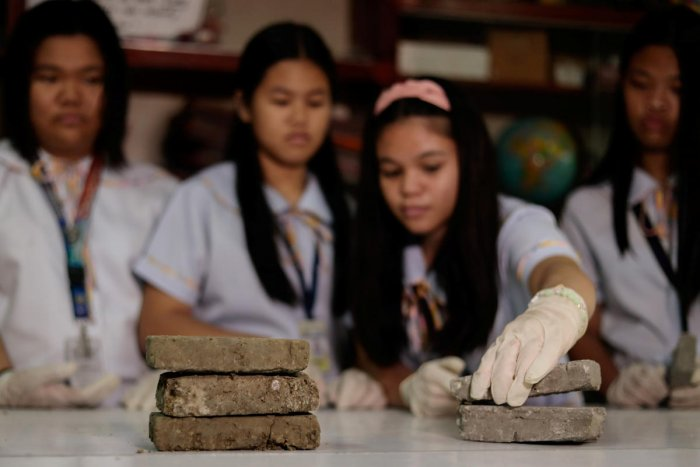 """Students pile their """"Bio-bricks"""" made of dog faeces and cement powder for demonstration, at Justice Cecilia Munoz Palma High School in Quezon City, Metro Manila, Philippines. (Reuters photo)"""