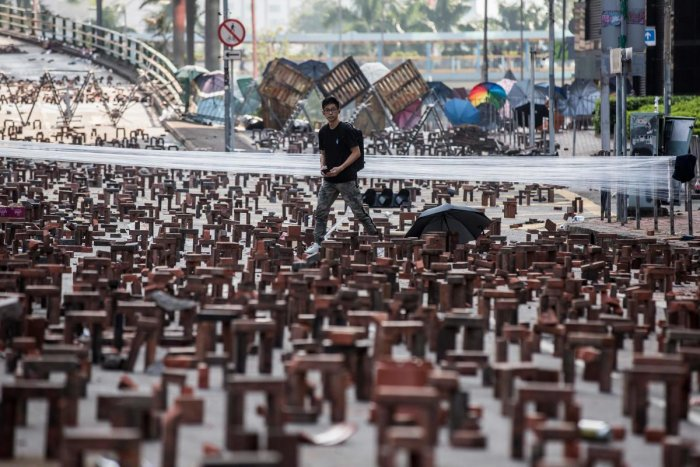 A man walks through bricks placed on a barricaded street outside The Hong Kong Polytechnic University in Hong Kong on November 15, 2019. - Pro-democracy protesters challenging China's rule of Hong Kong on November 14 choked the city for a fo