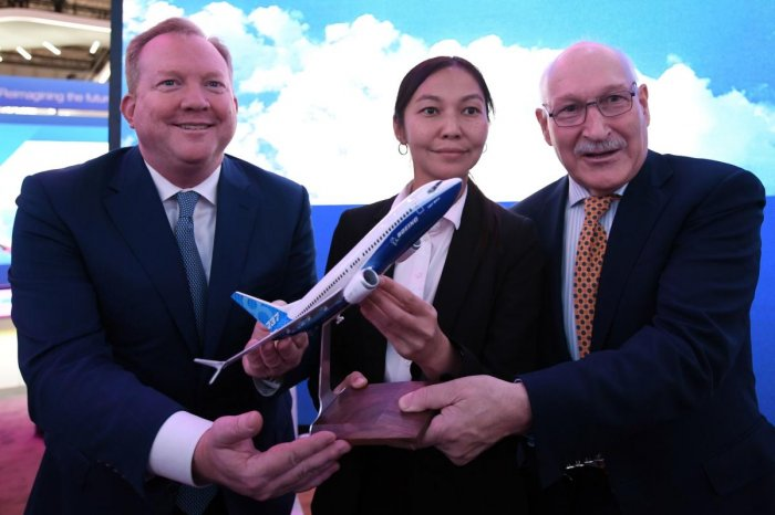 Stanley Deal (L), President and Chief Executing Office at Boeing, poses for a picture with Alma Aliguzhinova (C), Chief Planning Officer at Air Astana, and Anthony Regan (R), Chief Operating Officer at Air Astana, after signing an agreement in Dubai. (Photo by AFP)