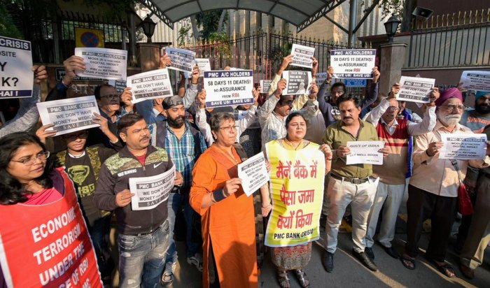 PMC bank account holders display placards as they protest outside the RBI building over the bank's crisis. (PTI Photo)
