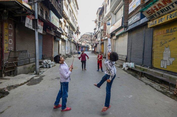 Children play badminton at a market during shutdown in Srinagar. (PTI Photo)