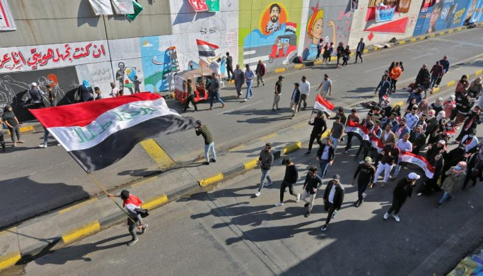 Iraqi youths waving national flags march through Tahrir Square in the Iraqi capital Baghdad as anti-government protests continued across the country. (Photo by AFP)