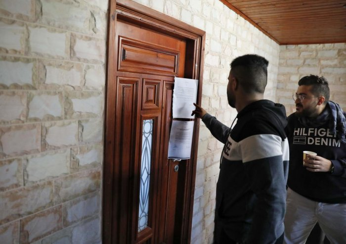 Palestinian employees of Palestine TV channel inspect a notice of closure at the door of the station's office after it has been raided by Israeli forces in East Jerusalem on November 20, 2019. - Israeli authorities ordered a six-months closure of multiple