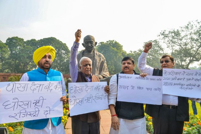 AAP MPs display placards demanding the introduction of a Bill to regularise unauthorised colonies of Delhi, during the Winter Session of Parliament (PTI photo)