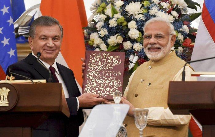 Prime Minister Narendra Modi is presented a book by Uzbek President Shavkat Mirziyoyev look on, at Hyderabad House in New Delhi on Monday. PTI
