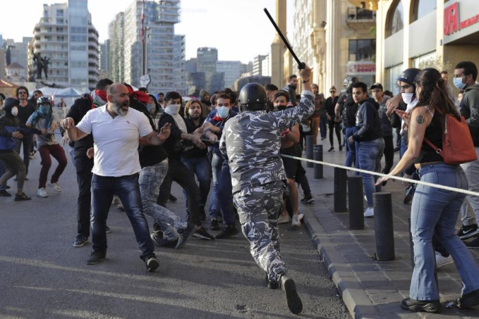 A police officer raises his baton to anti-government protesters during clashes during a protest in downtown Beirut, Lebanon. (AP/PTI Photo)