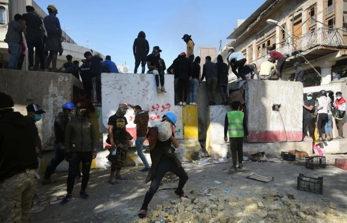 Iraqi anti-government protesters clash with security forces in al-Rasheed street near al-Ahrar bridge. (Photo by AFP)