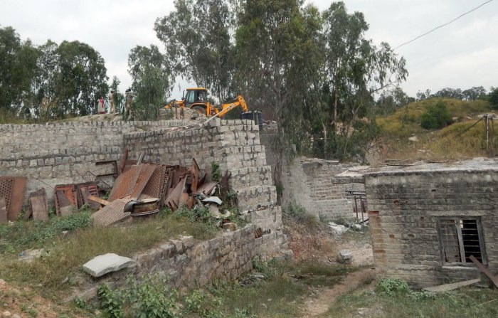 Forest department officials demolish the structures with excavators, at the illegal crushing units in Srirangapatna, Mandya district on Friday.