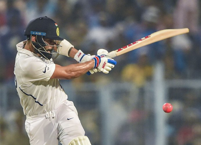 Indian Skipper Virat Kohli plays a shot during the 1st pink-ball day/night cricket test match between India and Bangladesh, at Eden Gardens in Kolkata. (PTI Photo)