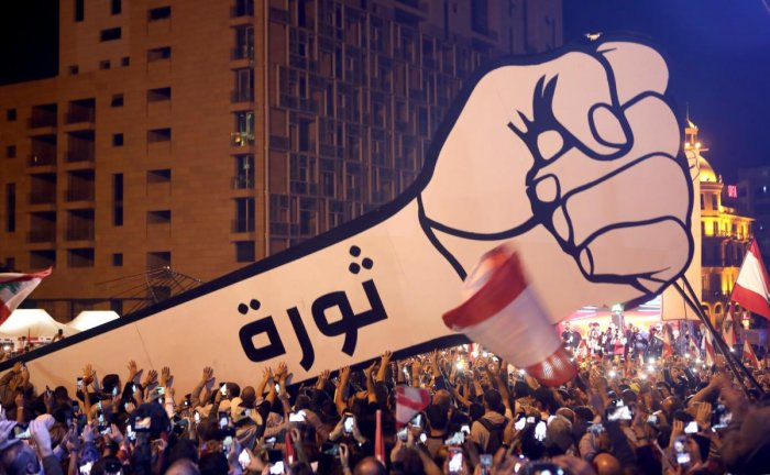 """Lebanese demonstrators raise a new giant sign of a fist that bears the Arabic word """"revolution"""" on it, in the Lebanese capital Beirut's Martyr's Square on November 22, 2019, after the sign was burnt overnight by unknown perpetrators."""
