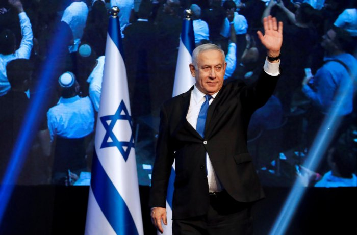 Israeli Prime Minister Benjamin waves to supporters at the Likud party headquarters.